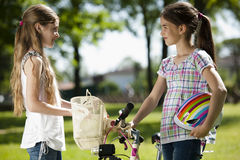 Friendhsip. Two little girls with bike outdoors Stock Image