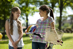 Friendhsip. Two little girls with bike outdoors Royalty Free Stock Images