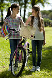 Friendhsip. Two little girls with bike outdoors Royalty Free Stock Photo