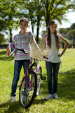 Friendhsip. Two little girls with bike outdoors Stock Photo