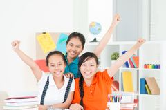 We are friendly!. Group of happy schoolmates sitting and looking at camera in a schoolroom Royalty Free Stock Photo