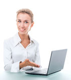 Friendly administrative assistant at the desk with a laptop. Young woman in office attire. The figure is isolated on a white background with the clipping path Stock Image