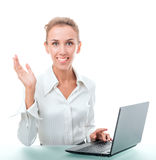 Friendly administrative assistant at the desk with a laptop Royalty Free Stock Photos