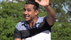 Friendly Adult Hispanic Man Waving. A handsome adult hispanic man stock footage