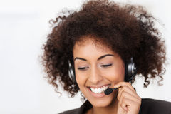 Friendly African American call centre operator. Wearing a headset in her curly hair smiling warmly as she listens to the conversation while helping a client Stock Images