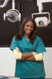 Friendly African-American dentist woman in office. Young smiling black ethnic Afro-American female dentist assistant standing in dental office by chair Stock Photo