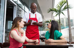 Friendly african american waiter with guests. In restaurant Royalty Free Stock Image
