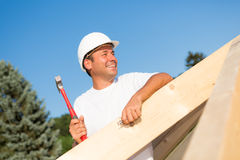 Friendly artisan working on a new house. Friendly artisan working hard to build the roof of a new house Royalty Free Stock Photo