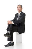Friendly Asian business man sit Royalty Free Stock Photo