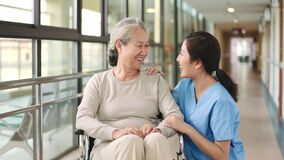 Friendly employee of nursing home talking to senior resident in hallway