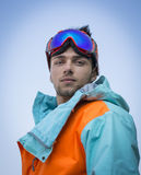 Friendly attractive skier or snowboarder against blue sky Royalty Free Stock Photos