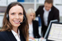 Friendly attractive young call centre operator. Or member of the client services team wearing a headset turning to give the camera a lovely warm smile Royalty Free Stock Photos