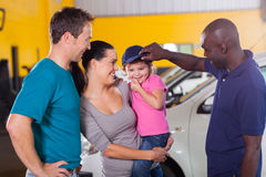 Friendly auto mechanic. Friendly african american auto mechanic playing with customer's little girl stock photo