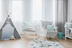 Friendly baby room decor in white and blue. Very bright baby boy`s room with white furniture and a toy wigwam royalty free stock photography