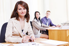 Friendly bank consultant. Sitting at the table Stock Photography