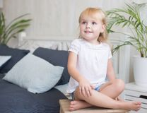 Friendly barefoot little girl sitting on a stool stock images