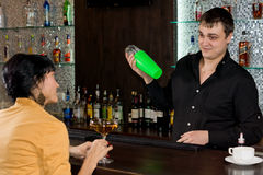 Friendly barman chatting to a female customer Stock Images
