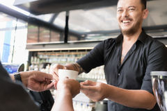 Friendly bartender serving espresso coffee to a customer in a mo Stock Image