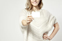 Friendly beautiful european woman holding a business card. And smiling. Focus on card Stock Photography
