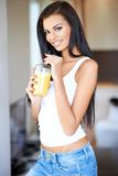 Friendly beautiful woman drinking orange juice Stock Images
