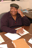 Friendly black man in office. Friendly middle age black man working in office with smile on telephone Royalty Free Stock Images