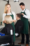 Friendly blonde cuts hair of mature woman Royalty Free Stock Photography