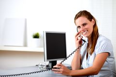 Friendly blonde secretary speaking on phone Stock Photo