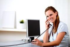 Friendly blonde secretary speaking on phone Stock Photo