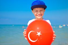 Friendly boy holding balloon with turkish flag on it royalty free stock photography