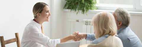 Horizontal image aged couple make deal handshaking with female realtor stock photo