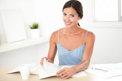 Friendly brunette female sitting and reading books Stock Photos