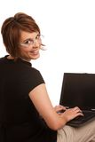 Friendly brunette female working on laptop. Young adult Caucasian female working on laptop and looking back over her shoulder while smiling Royalty Free Stock Images