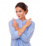 Friendly brunette with lucky sign smiling at you Stock Photo