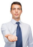 Friendly buisnessman showing something on the palm. Business and office, advertising, people concept - friendly young buisnessman showing something on the palm Royalty Free Stock Image