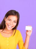 Friendly business card woman. Business card woman showing friendly smile. Beautiful cute mixed race caucasian / chinese young woman model presenting a blank Royalty Free Stock Image