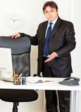 Friendly business an inviting to sit on chair. Friendly modern business man inviting to sit on office chair Stock Photo