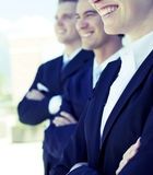 Friendly business team. Three businesspeople standing and smiling in same direction Stock Image