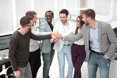Friendly business team putting their hands together stock images