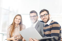 Friendly business team working on laptop and discussing business matters Royalty Free Stock Image