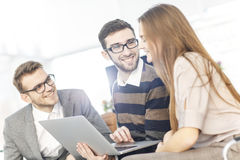 Friendly business team working on laptop and discussing business matters Stock Image