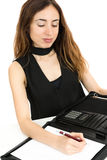 Friendly business woman writing notes at the office desk Royalty Free Stock Image
