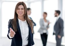 Friendly business woman holding out her hand for a handshake stock photography