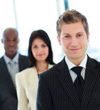 Friendly businessman in front of his team Stock Photo