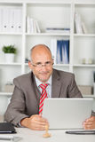 Friendly businessman sitting at desk with laptop Stock Image