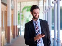 Friendly businessman smiling with mobile phone Royalty Free Stock Photo