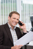 Friendly businessman talking on his mobile Stock Image