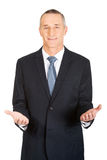 Friendly businessman with welcome gesture Stock Images