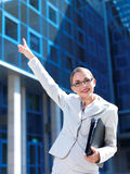 Friendly businesswoman pointing to the office Stock Images