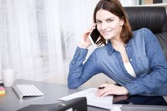 Friendly businesswoman smiling as she takes a call Stock Images