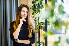 Friendly businesswoman standing with hands in a bright office looking at the camera Royalty Free Stock Photography